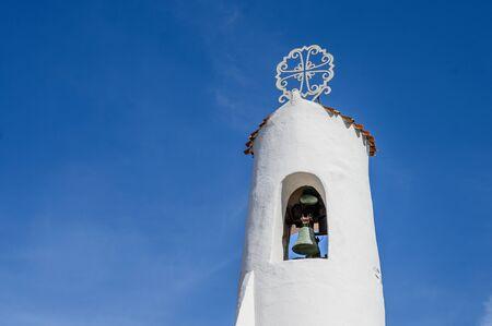 Ancient white bell tower against the blue sky. Porto Cervo, Sardinia