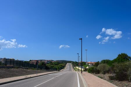 Road goes into the distance against a blue sky with clouds. On the sides trees and a small village