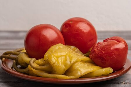 Assorted pickled peppers and tomatoes on a ceramic plate on a wooden background