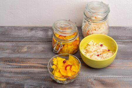 Homemade sauerkraut in glass jars and salad bowls on a wooden background. Rustic style Stockfoto - 131326511