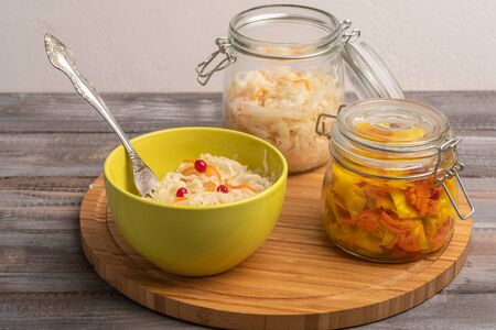 Homemade sauerkraut in two jars with a salad bowl and a fork on a wooden board. Rustic style