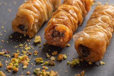 Traditional greek pastries saragli with pistachios on dark background