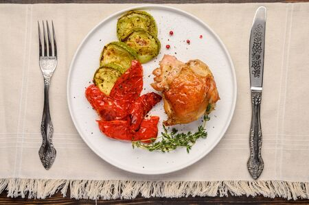 Homemade baked chicken thigh, zucchini and peppers with soy sauce, spices and herbs on a white plate on a linen napkin with a knife and fork. Rustic style Standard-Bild - 134948771
