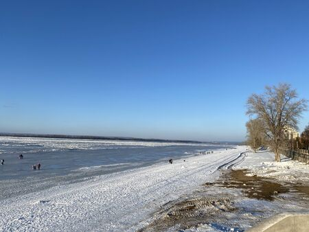View from the embankment to the frozen Volga River in Samara, Russia. In the distance, people walk on the ice on a sunny day Stock Photo