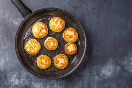 Homemade toasted cheesecakes in a frying pan on a dark wooden background. Top view. Copy space Фото со стока