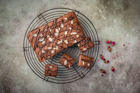 Homemade brownie with chocolate and almond petals. Top view. Copy space. Flat lay food