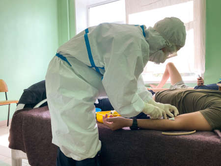 Doctor in a protective suit in the hospital injects a coronavirus patient into a vein, close up