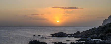 Panorama of sunrise over sea. The suns rays are reflected in the clouds. In the foreground a rocky shore. Copy space 写真素材