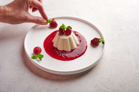 Womans hand puts raspberry to panna cotta with syrup, berries and mint, high key, close up 版權商用圖片