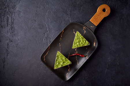 Verrines from baked pepper with gorgonzola and pesto in transparent buffet shape cup on black rectangular dessert plate on dark background. Top view