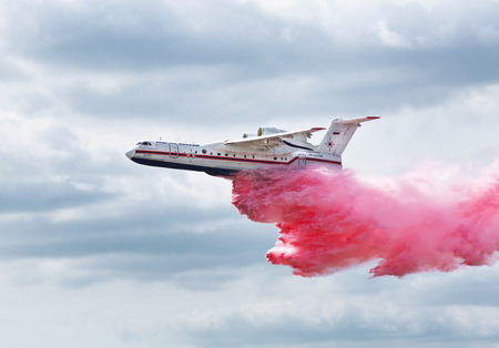 amphibious: ZHUKOVSKY, RUSSIA - AUGUST 28, 2015: International aviation and space salon in Zhukovsky. Amphibian aircraft B200 flies and demonstrates the discharge of water when extinguishing the fire