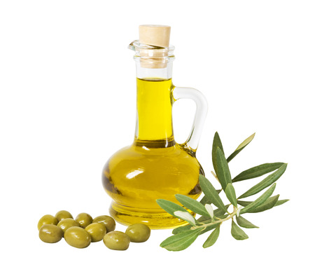 Glass bottle of premium olive oil and some olives with a branch isolated on white background