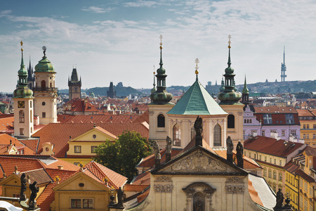 stare mesto: View of the roofs of Prague, with red tiled roofs and  statues, spires and towers protruding
