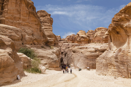 siq: Tourists in narrow passage of rocks of Petra canyon in Jordan. Petra has been a UNESCO World Heritage Site since 1985. Way through Siq gorge to stone city Petra
