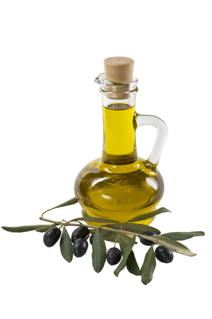 olive green: Glass bottle of premium olive oil and some ripe olives with a branch isolated on white background
