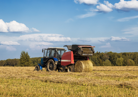 MOSCOW REGION, RUSSIA - AUGUST 21, 2016: harvesting hay in a field on a summer day Editorial