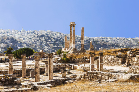 The ruins of the Temple of Hercules in Amman, the ancient fortress on a background of the urban landscape, Jordan