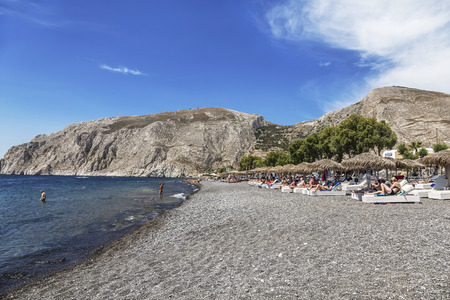 Beach with grey volcanic sand at Kamari, Santorini island, Greece
