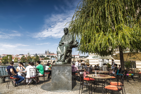 Tourists in cafes on the banks of the Vltava river near the monument to famous czech composer Bedrich Smetana infront of The Bedrich Smetana Museum., Prague, Czech Republic