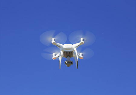Quadrocopter with digital camera flying against the blue sky