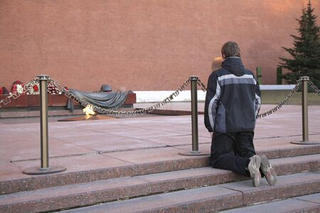 MOSCOW, RUSSIA - APRIL 09, 2009: The Eternal flame near Kremlin wall in the Alexander garden. The young man knelt down as a sign of respect and memory of the soldiers who died during the Great Patriotic war. Moscow, Russia