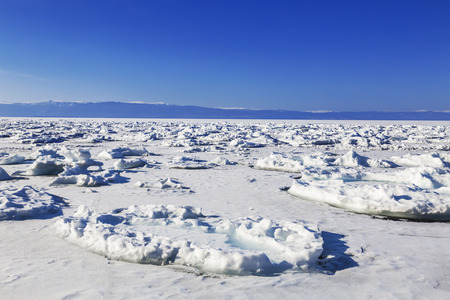 View of the frozen lake Baikal on a Sunny day. Irkutsk region, Russia