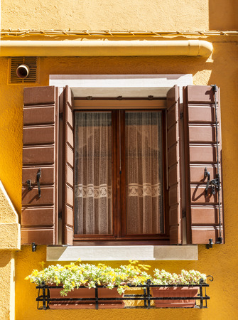 A window with open shutters and flowers in a drawer underneath. A house on Burano island, Venice, Italy