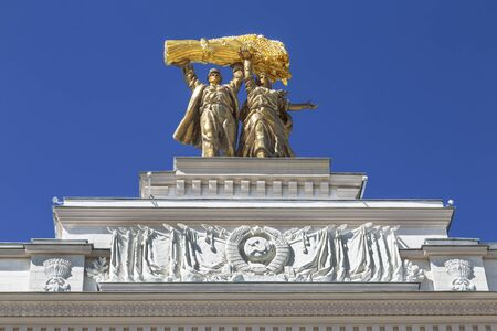 Sculpture of a tractor driver and a collective farmer on the arch of the main entrance at VDNH, Moscow, Russia