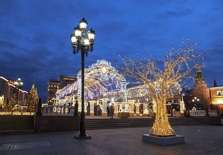 Manezhnaya square during New Year and Christmas holidays with glowing multi-colored arch and trees at night, Moscow, Russia