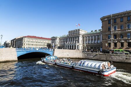 View of the Blue bridge over the Moika river and a tourist boat floating on the river, St. Petersburg, Russia