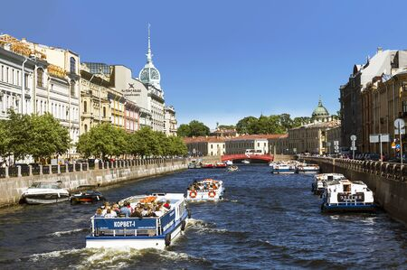 View of the embankments of the Moika river, tourist boats, the Red bridge and the Trading house S. Esders and K. Skheifals in Saint-Petersburg, Russia Editöryel
