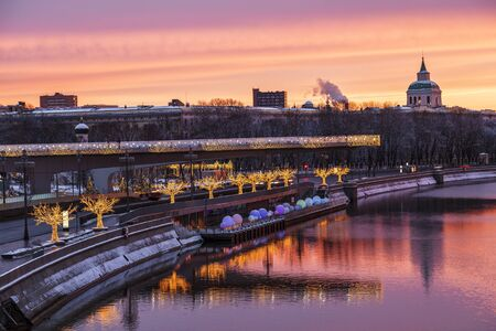 View of Zaryadye Park with soaring bridge, Moscow river with reflection in the water at dawn on new year and Christmas holidays. Moscow, Russia Editöryel