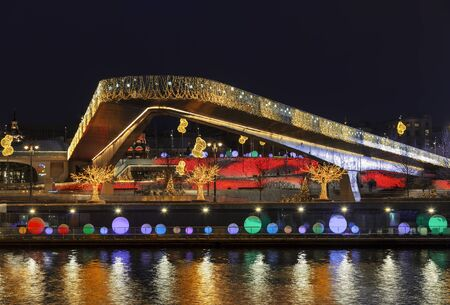 View of Christmas Moscow with a soaring bridge over the Moscow river, new year installations in the form of glowing trees and colorful glowing balls on Moskvoretskaya embankment. Russia