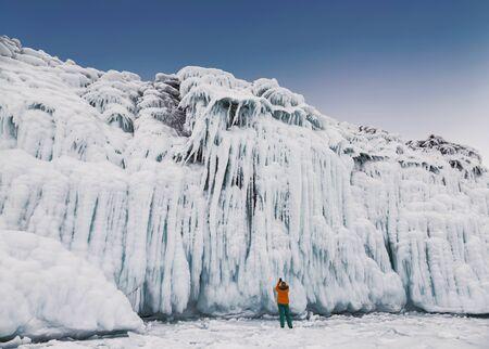 Fabulous ice icicles on the rocks of lake Baikal. Tourist photographs the icy rocks. Eastern Siberia, Russia