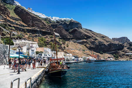 Tourists and tourist ship in the old port in Fira, Santorini, Greece