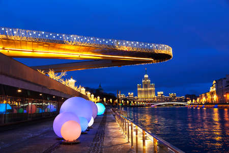 View of Christmas Moscow with a soaring bridge over the Moscow river, new year installations and a high-rise building on Kotelnicheskaya embankment on the horizon. Russia