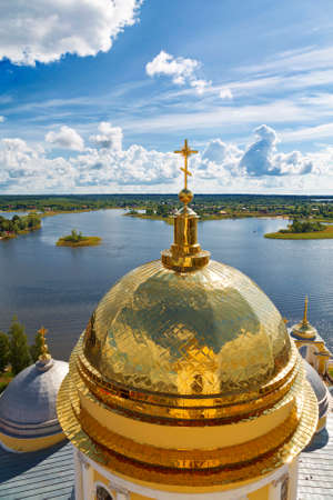 Top view of the golden domes of the Epiphany cathedral nilo-Stolobenskaya desert on the background of lake Seliger. Tver Region, Russia