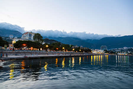 View of the evening embankment in Yalta with walking tourists. Crimea, Russia