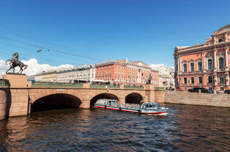 View of Anichkov bridge over the Fontanka river and tourist boat floating on the river, St. Petersburg, Russia