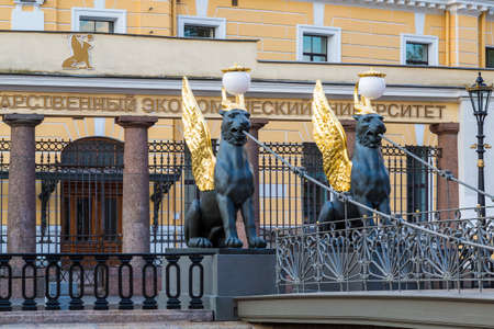 View on griffins on the Bank bridge over the Griboyedov canal against the background of the building of the State University of Economics in St. Petersburg. Russia Standard-Bild