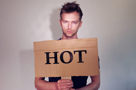 man holding sign: Hot man holding sign with text Stock Photo