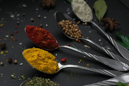 Set of various spices and herbs on black slate background. Pepper, turmelic, ginger, saffron, basil, rosemary, chilly, cardamom, cinnamon, anise. Top view with copy space. 写真素材