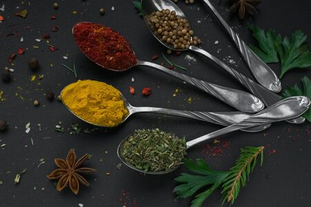 Set of various spices and herbs on black slate background. Pepper, turmelic, ginger, saffron, basil, rosemary, chilly, cardamom, cinnamon, anise. Top view with copy space. Imagens