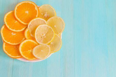Cut slices of orange and lemon on a plate on a blue wooden background close-up. Concept healthy vitamin vegan food. Refreshing citrus. copy space Stock Photo