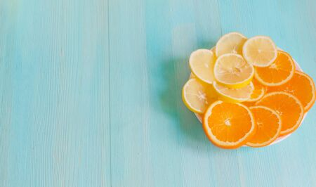 Cut slices of orange and lemon on a plate on a blue wooden background close-up. Concept healthy vitamin vegan food. Refreshing citrus. copy space Stock Photo - 124978056