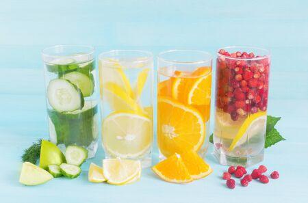 蓝色背景下多汁水果的柠檬汁。夏日鸡尾酒,柠檬,浆果,黄瓜,橙子,高脚杯清爽的饮料,素食,新鲜的维生素。本空间
