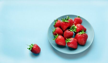 fresh strawberries in a bowl on the table. summer fruits and berries. Delicious breakfast. Healthy food. Vitamins. Vegetarian food. Diet. blue background.
