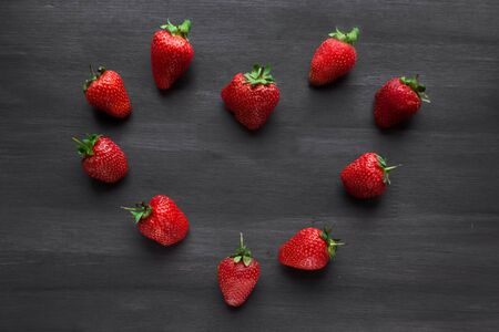 ripe fresh strawberries in the shape of a heart on a black wooden table. summer fruits and berries. The concept of a Delicious Breakfast. Health food. Vitamin complex. Vegetarian food. Diet. black background. close up. copy space
