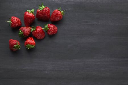 ripe fresh strawberries on a black wooden table. summer fruits and berries. The concept of a Delicious Breakfast. Health food. Vitamin complex. Vegetarian food. Diet. black background. close up. copy space