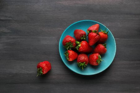 fresh strawberries in a bowl on the table. summer fruits and berries. Delicious breakfast. Healthy food. Vitamins. Vegetarian food. Diet. black background. Banco de Imagens